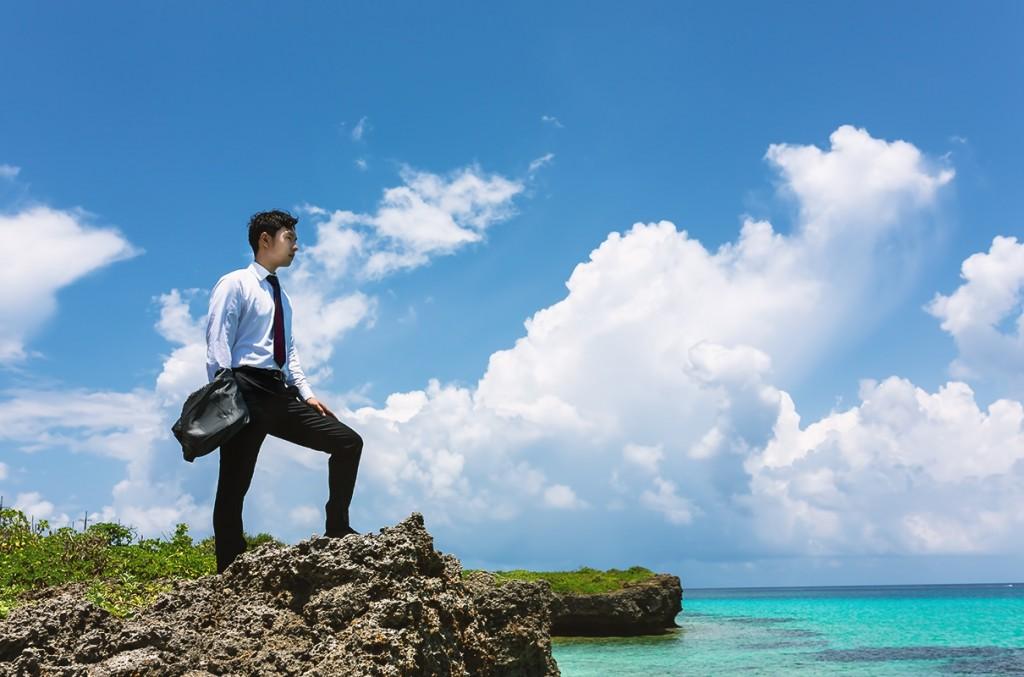 宮古島の風景をバックに達成感を味わう男性